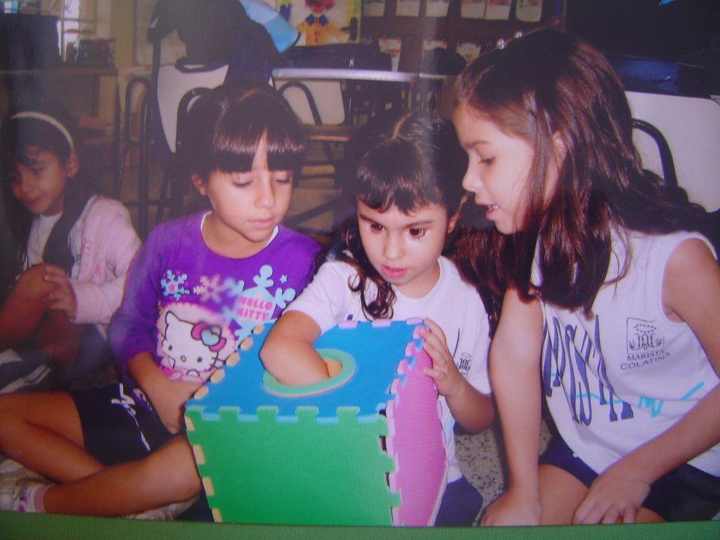 Foto 1: Laura com as colegas na escola brincando com uma caixa surpresa , elas pegam um objeto dentro da caixa e tentam adivinhar o que é antes de retirá-lo .
