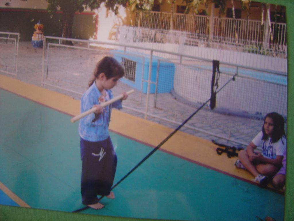 Foto 2: Laura na escola em atividade de equilibrismo no projeto circo, andando em cima de uma corda e segurando um bastão.