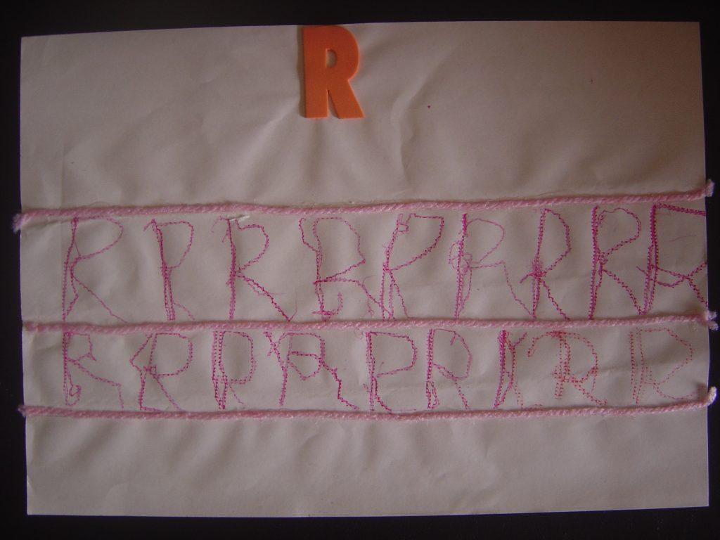 Foto 3: Papel com linhas feitas em relevo , e um espaço entre elas de cerca de 3,0 cm e colocado em uma prancheta forrada que produz relevo no que é escrito sobre ela . Uma letra R em EVA foi colada no papel. E a Laura vai escrevendo a letra R observando o modelo e percebendo o traçado do que escreve.