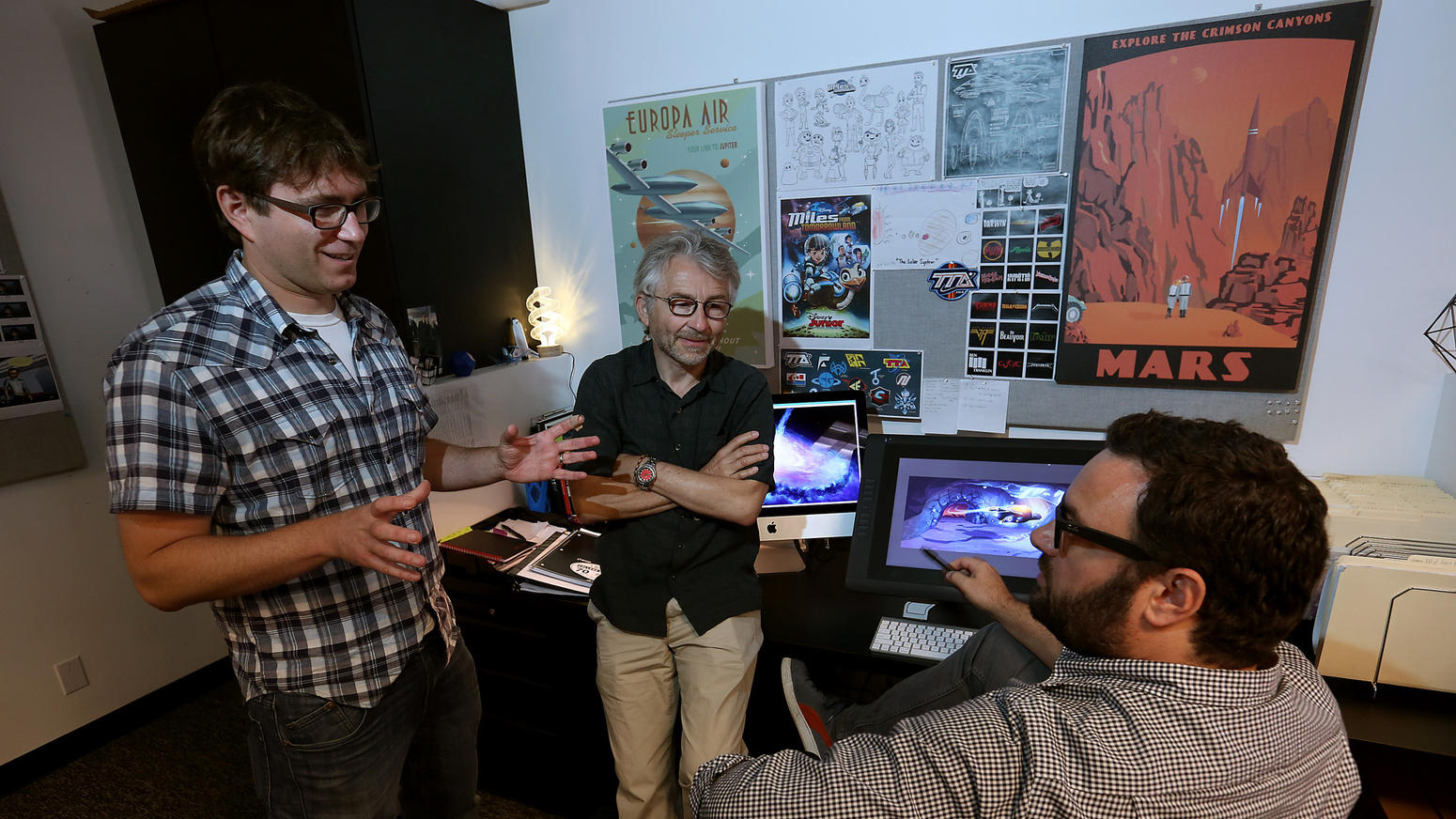 """Paul Demeyer Kirk McKoy / Los Angeles Times Paul Demeyer, center, talks with Sascha Paladino (creator and executive producer), left, and Max Miceli (art director) on scenes in Disney's """"Miles from Tomorrowland."""""""