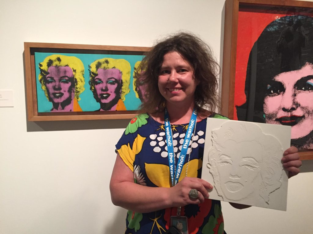Leah Morelli of the Andy Warhol Museum holds a tactile reproduction of Warhol's classic screenprinted painting of Marilyn Monroe. Credit Virginia Alvino / 90.5 Wesa
