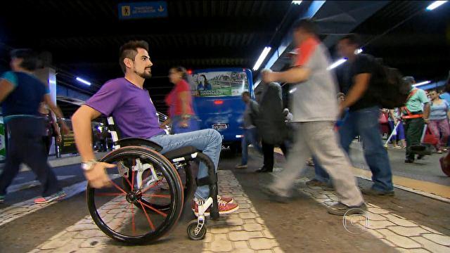 Homem sentando na cadeira de rodas vestindo uma camisa roxa, calça jeans e vultos de pessoas caminhando de diversas direções
