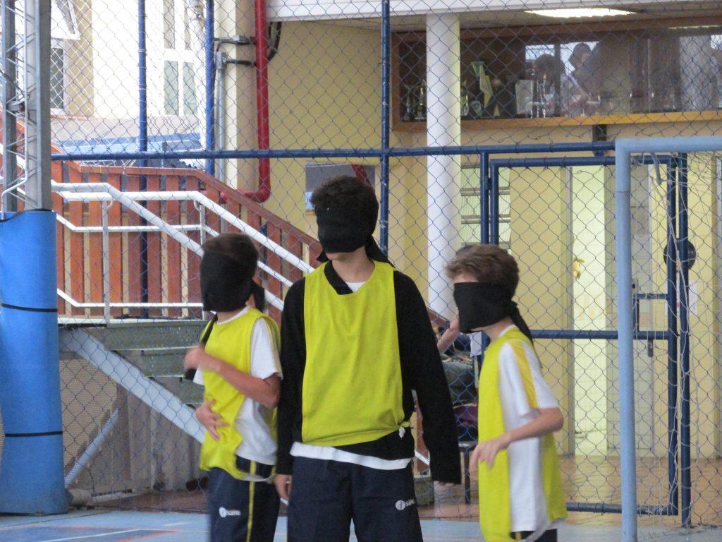 Crianças com os olhos vendados usando camisas amarelas