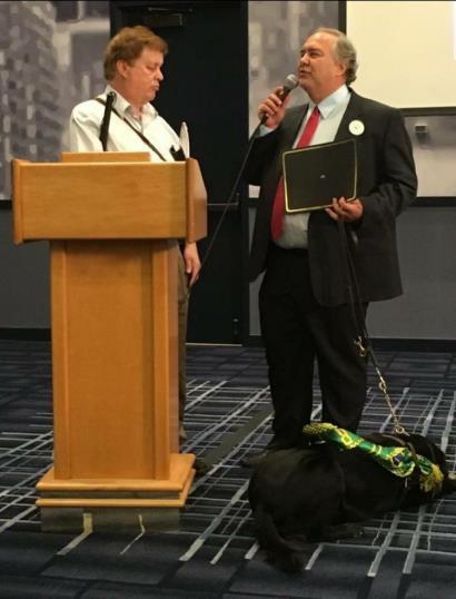 De pé, trajando terno preto sobre camisa azul claro e gravata vermelha, o professor Francisco segura a placa de premiação Barry Levine. Deitada, junto ao pé esquerdo do professor, a cão-guia Okra, de arreio e faixa verde e amarela, volta-se para trás. Okra é uma Labrador preta, de pelos brilhantes.